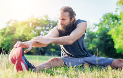 Fit fitness man stretching exercises outdoors Stock Image