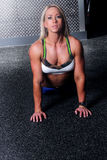 Fit fitness woman doing a lower back stretch. Image of a beautiful female doing a back stretch at the gym Stock Photos