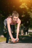 Fit fitness woman doing stretching exercises outdoors at park Royalty Free Stock Image