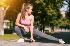 Fit fitness woman doing stretching exercises outdoors at park Royalty Free Stock Photography