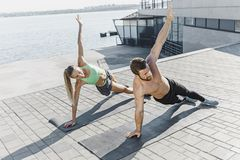 Fit fitness woman and man doing fitness exercises outdoors at city stock images
