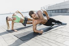 Fit fitness woman and man doing fitness exercises outdoors at city royalty free stock photos