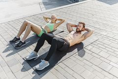 Fit fitness woman and man doing fitness exercises outdoors at city royalty free stock image
