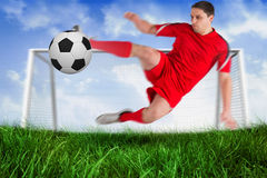 Fit football player jumping and kicking ball Royalty Free Stock Photography
