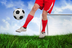 Fit football player kicking the ball Royalty Free Stock Photography
