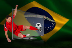 Fit football player kicking ball through tv Stock Photo