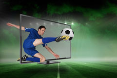 Fit football player kicking ball through tv Royalty Free Stock Photo