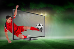 Fit football player kicking ball through tv Stock Image