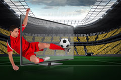 Fit football player kicking ball through tv Stock Photos