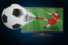 Fit football player playing and kicking ball out of tv Royalty Free Stock Image