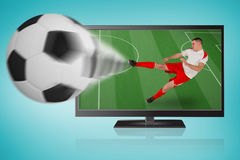 Fit football player playing and kicking ball out of tv Stock Images