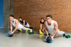 Fit four sportsmen exercising with equipment Royalty Free Stock Image