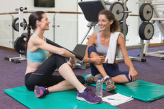 Fit friends chatting together on exercise mats Stock Image