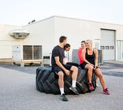 Fit Friends Conversing While Relaxing On Tire. Group of fit friends conversing while relaxing on tire after workout outdoors royalty free stock photography