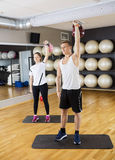 Fit Friends Lifting Kettlebells In Gym Royalty Free Stock Photography