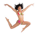 Fit girl in bikini leaping and smiling at camera Royalty Free Stock Images