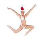 Fit girl in bikini smiling at camera wearing santa hat Stock Image