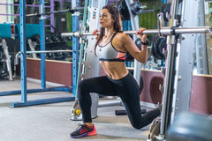 Fit girl doing lunges with the smith machine Stock Photo