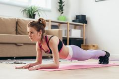 Fit girl doing plank exercise at home. Stock Image