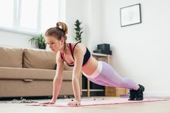 Fit girl doing plank exercise at home. Stock Photos