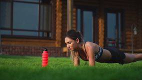 Fit girl doing plank exercise outdoor in the park warm summer day. Concept of endurance and motivation.  stock footage