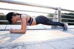 Fit girl doing plank exercise outdoor in the park warm summer day. Concept of endurance and motivation. royalty free stock photography