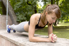 Fit girl doing plank exercise outdoor in the park warm summer day. Concept of endurance and motivation.  stock images