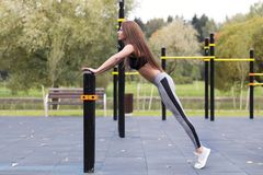 Fit girl doing plank or push-up exercise outdoor in the park warm summer day. Concept of endurance and motivation.  Royalty Free Stock Image