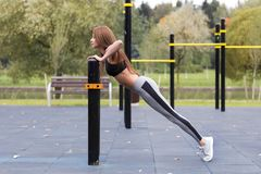 Fit girl doing plank or push-up exercise outdoor in the park warm summer day. Concept of endurance and motivation royalty free stock photos