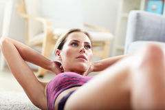 Fit girl doing sit-ups at home in the living room Stock Photos