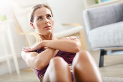 Fit girl doing sit-ups at home in the living room Stock Image