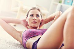 Fit girl doing sit-ups at home in the living room Stock Photo
