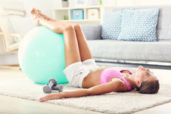 Fit girl doing sit-ups at home in the living room Royalty Free Stock Photos