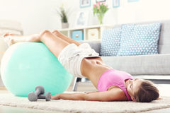 Fit girl doing sit-ups at home in the living room Stock Photography