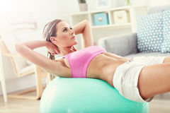 Fit girl doing sit-ups at home in the living room Royalty Free Stock Image