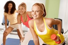 Fit girl exercising with dumbbells smiling. Fit girl exercising with dumbbells in group, smiling Royalty Free Stock Image