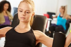 Fit girl exercising at the gym. Doing arm exercises Stock Photography