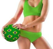 Fit girl in green bikini holding brazil ball Royalty Free Stock Photos