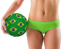 Fit girl in green bikini holding brazil football Royalty Free Stock Image