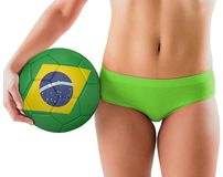 Fit girl in green bikini holding brazil football Stock Image