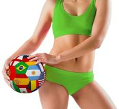 Fit girl in green bikini holding flag ball Stock Images