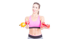 Fit girl holding fruits and weights as balance Stock Photography
