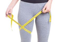 Fit girl holding tape line around leg Royalty Free Stock Photos