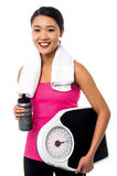 Fit girl holding weight scale and sipper bottle Royalty Free Stock Photo