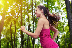 Fit girl jogging in the park on sunny day stock photo