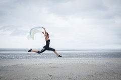 Fit girl leaping with scarf Stock Photos