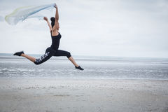 Fit girl leaping with scarf Royalty Free Stock Images