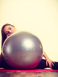 Fit girl lifting ball. Fitness health activity sport gym concept. Fit girl lifting ball. Young sporty lady exercising with training gear Royalty Free Stock Photo