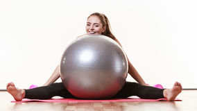 Fit girl lifting ball. Fitness health activity sport gym concept. Fit girl lifting ball. Young sporty lady exercising with training gear Stock Images