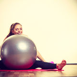 Fit girl lifting ball. Fitness health activity sport gym concept. Fit girl lifting ball. Young sporty lady exercising with training gear Stock Photo